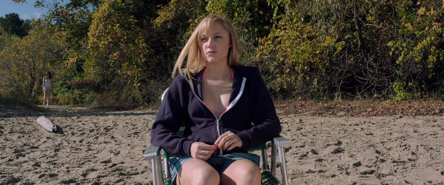 Jay (Maika Monroe) sits in a deck chair on the beach, while a figure in white in the background approaches her. From 'It Follows'
