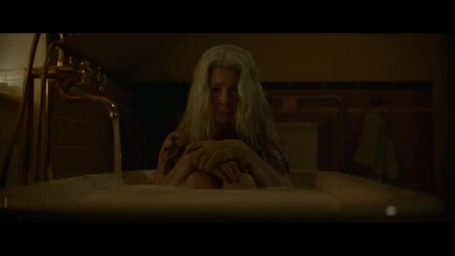Edna (Robyn Nevin) sitting in a bathtub in a dimly lit bathroom. Screenshot from Relic (2020)