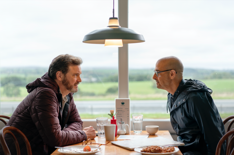 Sam (Colin Firth) and Tusker (Stanley Tucci) converse over a restaurant table in a motorway diner.
