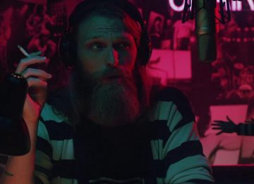A bearded man, wearing a striped black and white top, sits in front of a radio microphone holding a cigarette. He is bathed in blue and red lighting and in the background are vague horror and band posters.