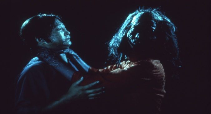Within complete darkness, a zombie with long hair grabs a man by the throat, who wears a panicked expression.